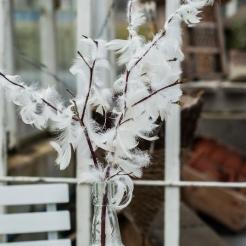 Fjädrar från en sönderklippt gammal dunkudde limmade direkt på en kvist. Foto: Johanne Pernklint